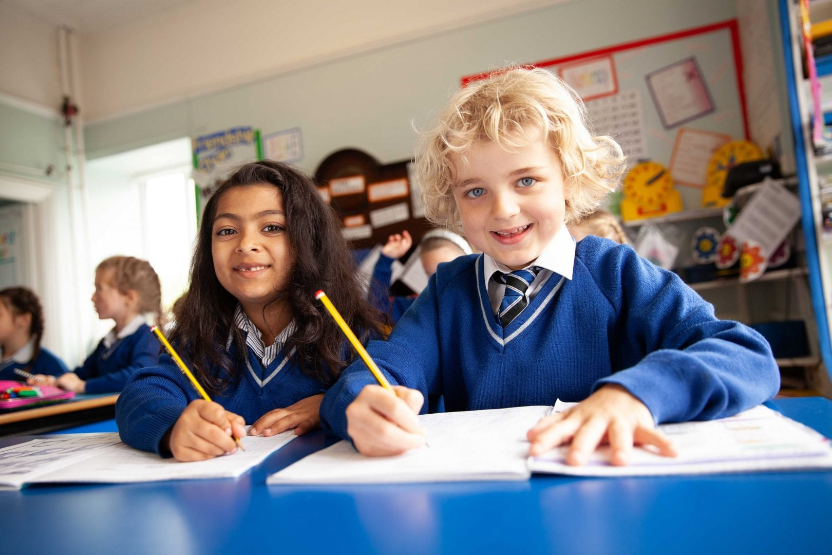 Girl and boy in royal blue uniform writing at a blue desk in their classroom at private independent school in Porthcawl, south Wales
