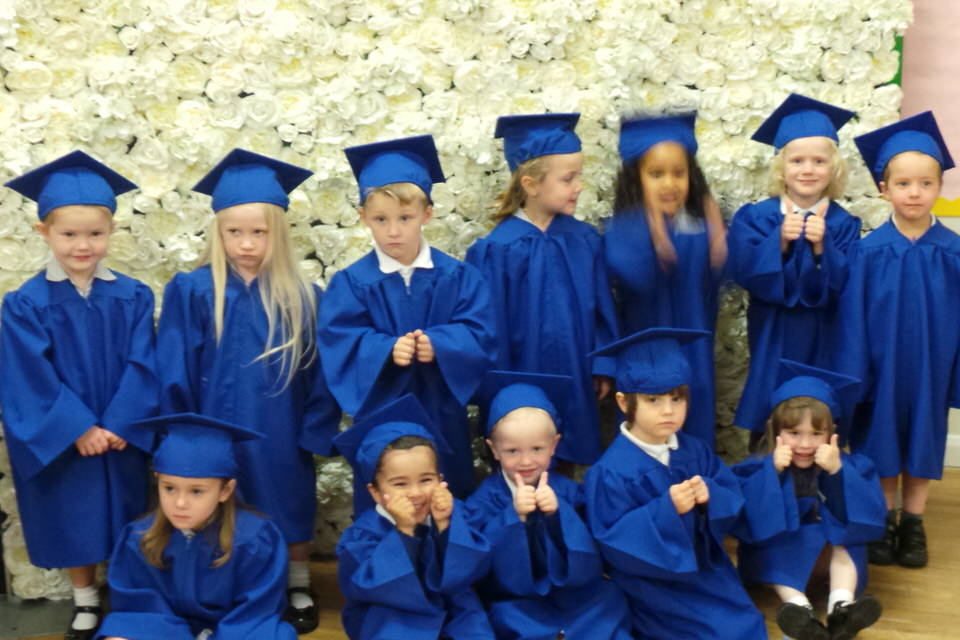 St Clare's Nursery pupils pose in their royal blue caps and gowns in front of the flower wall