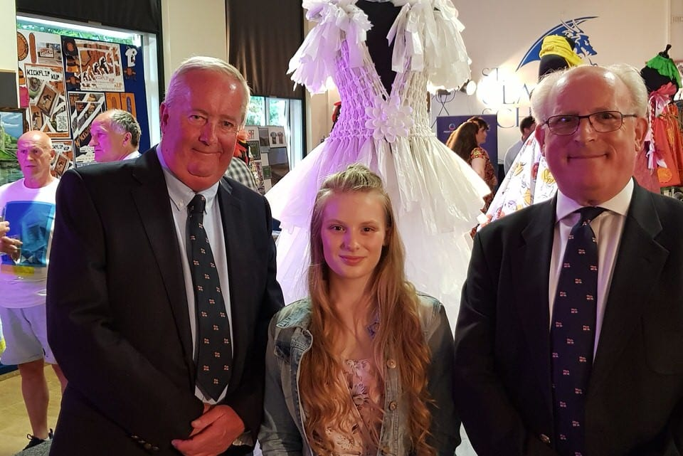 Two men in dark suits and RNLI ties stand either side of A-Level Textiles student, with her wedding dress in the backgrundand on either