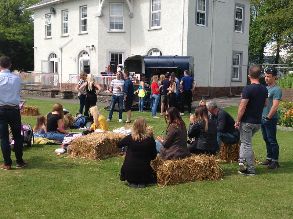 Families sitting on hay bales listening to band at community fun day at private school in Porthcawl, South Wales