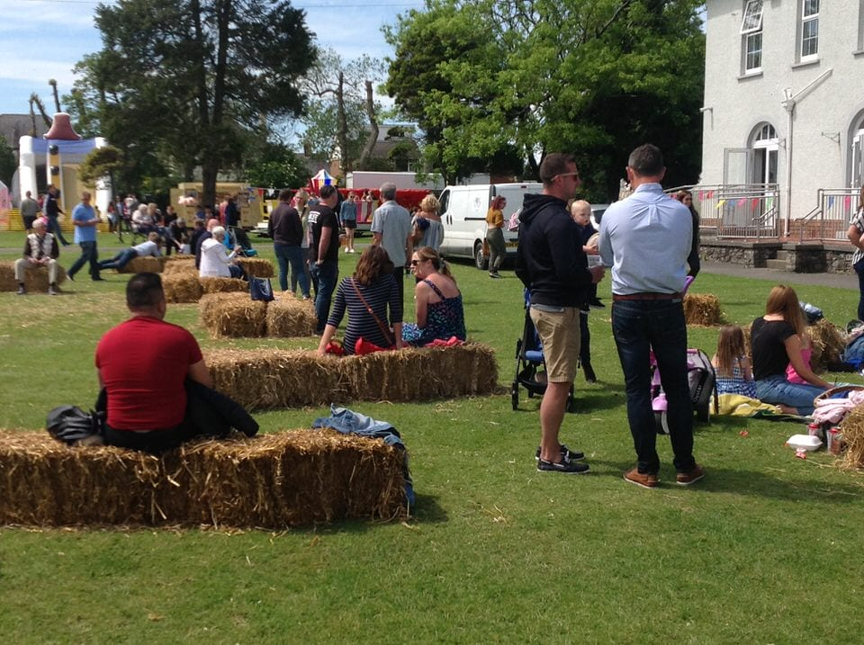 Groups of people chatting at community fun day at private school in Porthcawl, South Wales