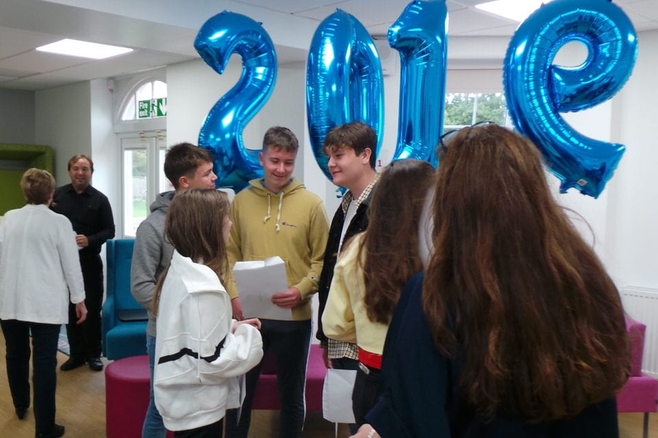 GCSE students stand beneath blue helium balloons spelling out 2019