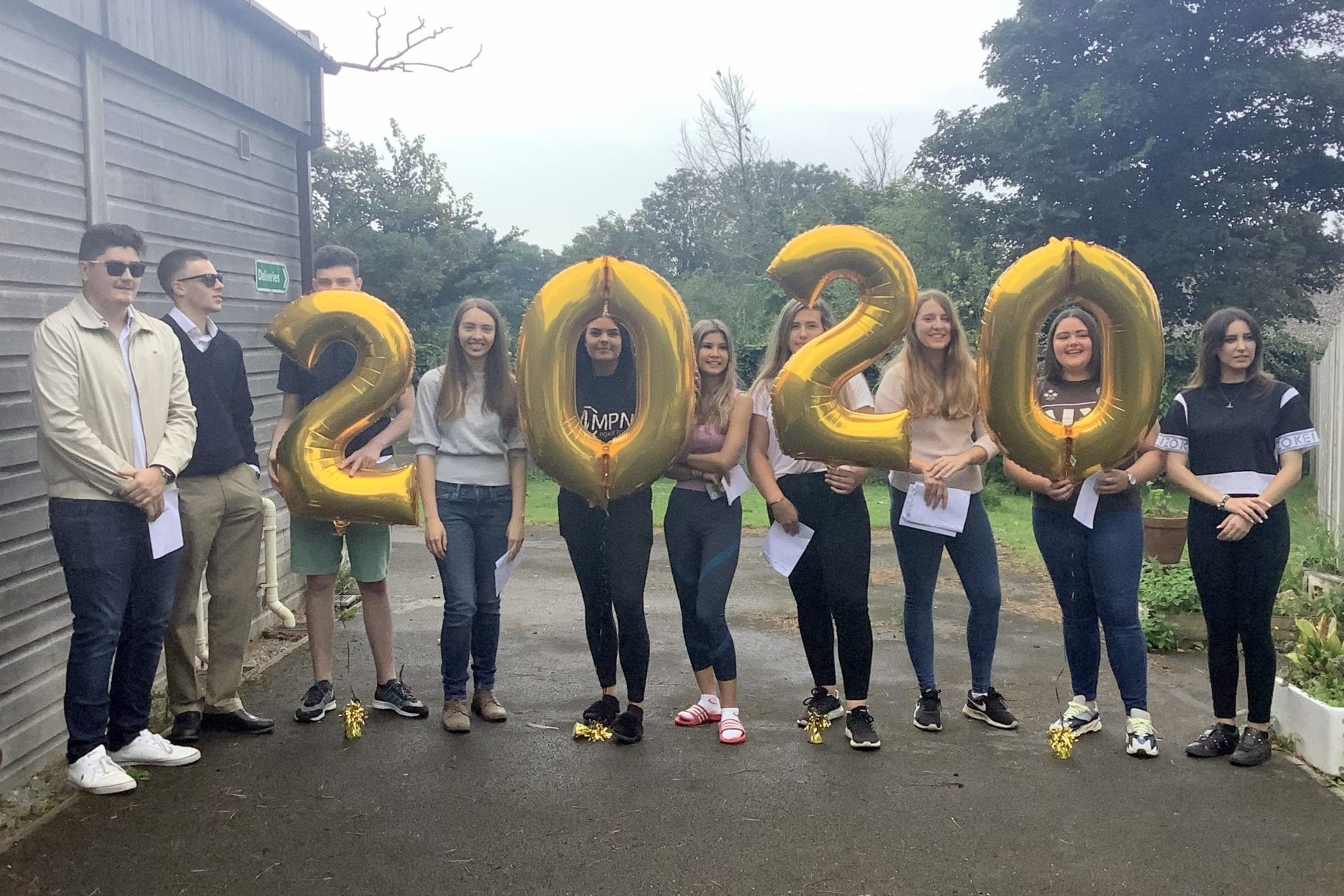 Teenage boys and girls holding up gold helium balloon numbers 2020